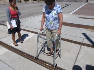 Image of woman with walker Crossing light rail tracks