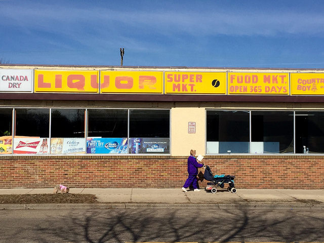 Woman walking in front of Danneckers Grocery & Liquor