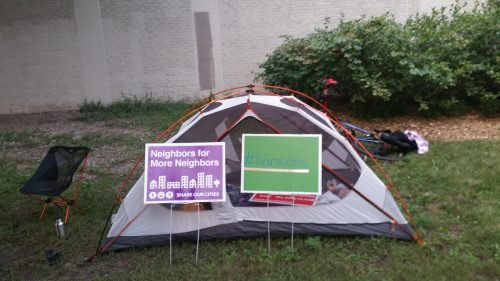A tent and two lawn signs. 'Neighbors for More Neighbors' and '#bancars'