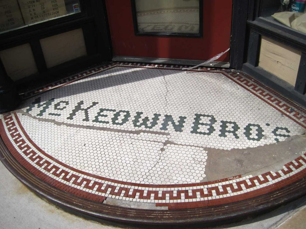 McKeown Bros letters in tile, white background, curved front on corner entry, red zigzag border