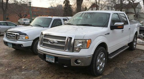 Smaller white Ford Ranger next to a large white Ford F150, almost twice as big