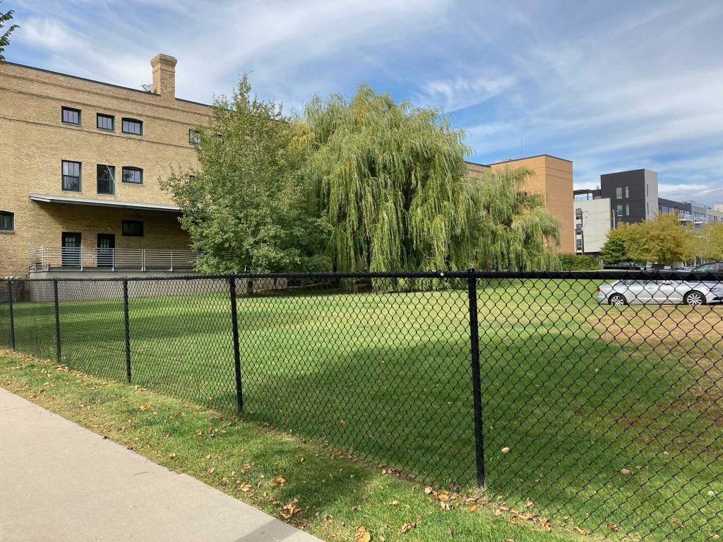 Carleton Lofts, brick apartment building with green lawn and some trees next door, enclosed by a black chain-link fence.
