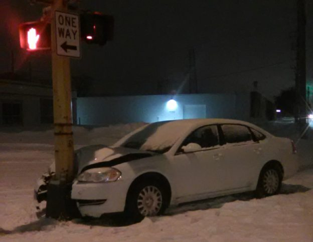 A white car that crashed into a traffic lightpost. It has a coating of snow on it.