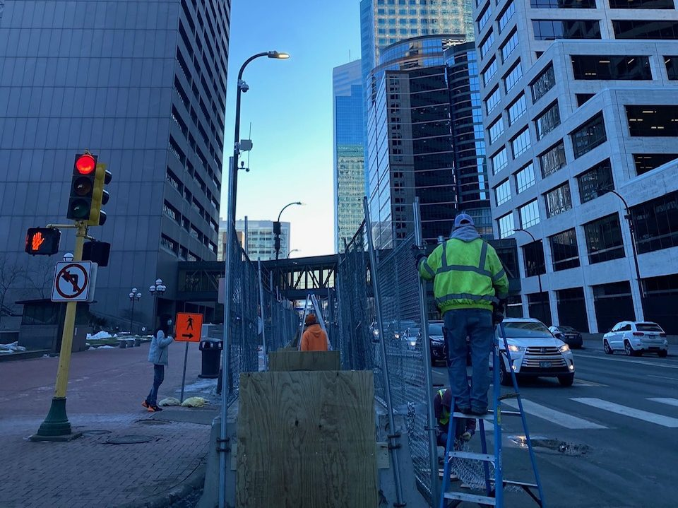 A construction worker in yellow puts up fences along a detour pedestrian path in downtown Minneapolis, with skyscrapers in the background against a clear blue sky